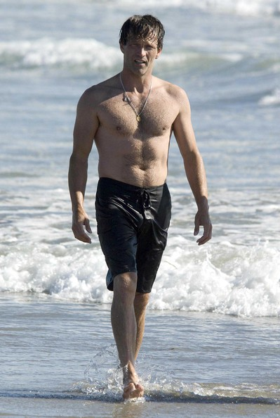 The Libra with shirtless athletic body on the beach